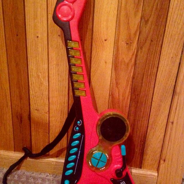 Toy guitar with keyboard, stop, demo, sound effect, tempo up and tempo down  buttons  25 inch long with strap  Battery operated  $5